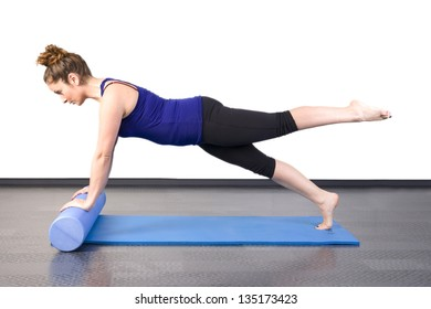 woman doing pilates on the floor with foam roller