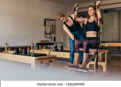 Woman doing pilates workout with stretch bands at the gym. Trainer guiding a pilates woman at gym for correct posture.
