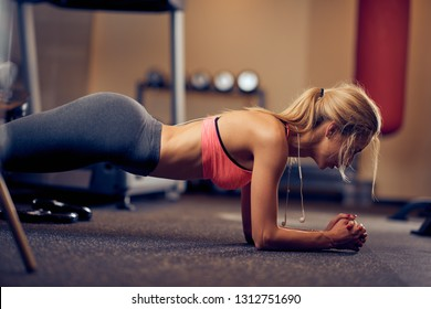 Woman doing planks on gym floor. Healthy lifestyle concept.