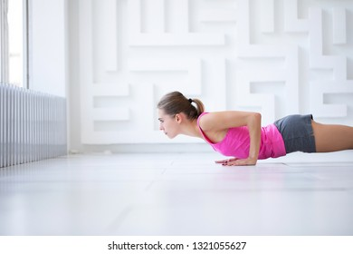 Woman doing press-ups during the training in the health club. Fit female.