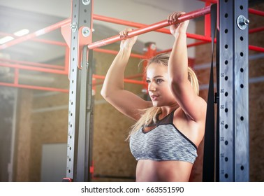 Woman doing pull ups on bar at the crossfit gym