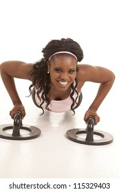 A woman doing a push up using push up bars.