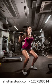 Woman doing quats while holding weight bar on her shoulders.