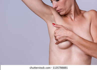 Woman doing a self examination of her breast checking for lumps or cancer tumours in a close up crop of her nude upper body over grey with copy space