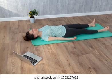 Woman doing Shavasana yoga pose at home during online yoga class