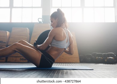 Woman doing sit ups with holding a weight plate. Fitness woman working out on core muscles at cross fit gym.