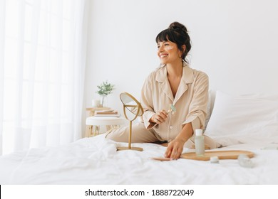 Woman doing skin care massage sitting on bed, Smiling woman using a roller to massage face.