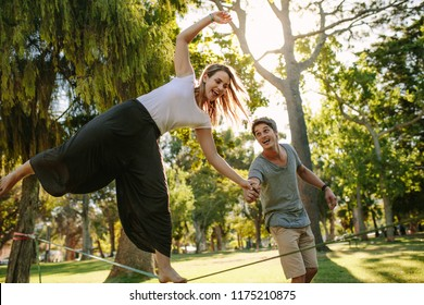 Woman doing slack rope walking in a park. Man helps woman in balancing during her tightrope walk in a park.