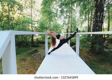 Woman doing split on a white wooden bridge in green park. Barre stretching outdoors.