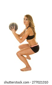 A woman doing a squat with her fitness ball in her hands.
