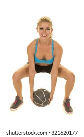 a woman doing a squat with a medicine ball
