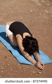 a woman doing a stretch on the beach.