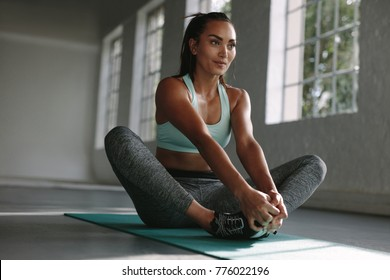 Woman doing stretches on exercise mat in gym. Baddha Konasana being performed by fitness female at gym. Cobbler pose stretching workout.