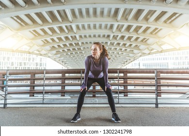 Woman doing stretching excercises, portrait with simmetry in urban industrial scene. Girl taking a rest during workout, simmetry with the architecture. Sport and fitness concepts