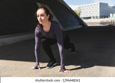 Woman doing stretching exercises in the city. Girl wearing sportswear doing fitness activities outdoors. Healthy lifestyle and sport concepts with urban industrial background