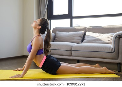 Woman doing stretching exercises during her workout at home