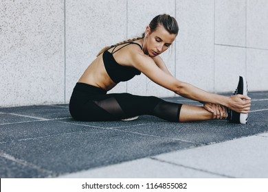 Woman doing stretching exercises listening to music wearing earphones. Fitness woman bending forward sitting on the ground and stretching her leg.