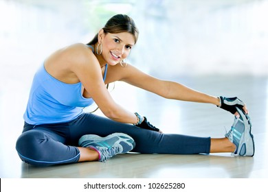 Woman doing stretching exercises on the floor at the gym