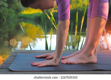 Woman doing stretching exercises on wooden pier at the lake. Healthy way of live