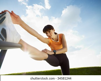 woman doing stretching outdoors at sunset. Low angle view, copy space