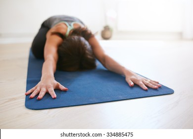 Woman doing stretching workout on fitness mat. Fit female performing yoga on exercise mat at gym. Child Pose, Balasana.