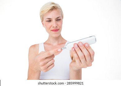 Woman doing test with blood glucose monitor on white background