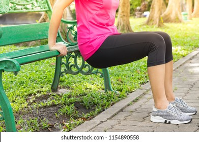 Woman doing triceps dips with bench in park.