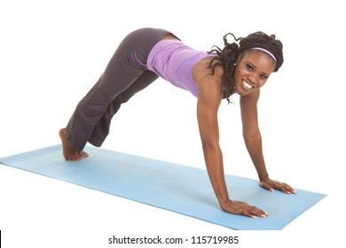 A woman doing a upward dog pose stretching her arms and legs with a smile on her face.