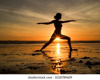 Woman doing Warrior Yoga Pose on a sunset beach