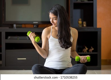 woman doing weights at home due to quarantine and coronavirus