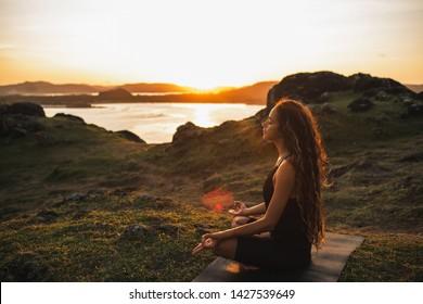 Frauen, die Yoga alleine bei Sonnenaufgang mit Blick auf Berge und Ozean machen. Harmonie mit der Natur. Selbstanalyse und Gewissensprüfung