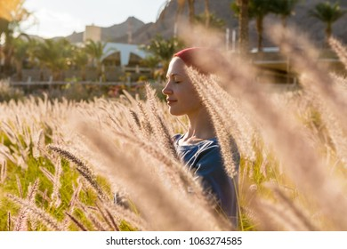 Woman doing yoga asana near sea in tall grass at tourist resort