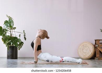 Woman doing yoga asana Urdhva mukha svanasana or upward facing dog pose on yoga mat in studio, Ashtanga Vinyasa, Surya Namaskar