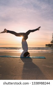woman doing yoga at the beach at sunset
