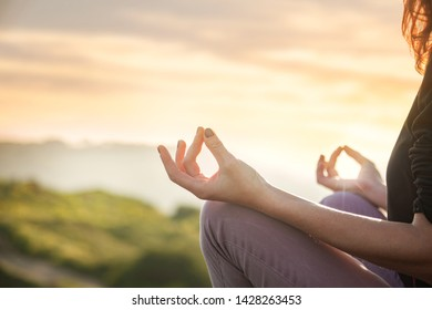 woman doing yoga in beautiful nature background at sunset or sunrise - mindfulness and mental health and hygiene background