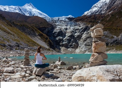 Woman is doing yoga excercises near big lake on the Manaslu circuit trak in Nepala