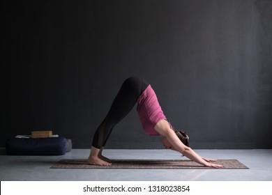Woman doing yoga exercise downward facing dog pose, adho mukha svanasana