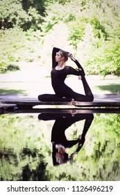 Woman doing yoga exercise. Yoga meditation near water. King of pigeons posture or eka pada rajakapotasana. Relaxation in nature. Sunlit photo