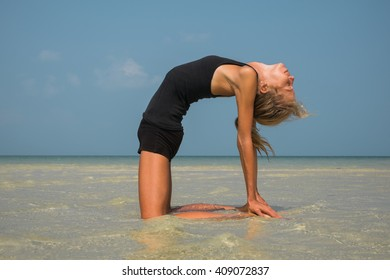 Woman doing yoga exercises by the sea
