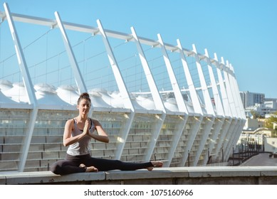 Woman doing yoga exercises outdoors at stadium.Beautiful brunette fit young woman wearing sportswear practicing yoga urban style.Asana, working out,fitness,sport,training and lifestyle concept