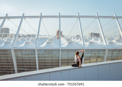 Woman doing yoga exercises outdoors at stadium.Beautiful brunette fit young woman wearing sportswear practicing yoga urban style. Asana, working out,fitness,sport,training and lifestyle concept