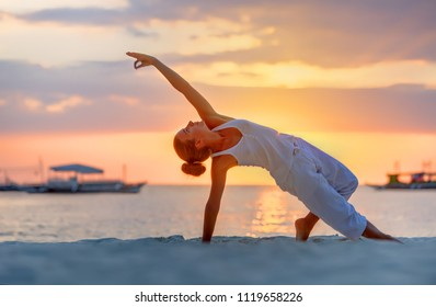 A woman is doing yoga exercises at the sunset on Boracay island, Philippines