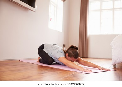 Woman Doing Yoga Fitness Exercises On Mat In Bedroom