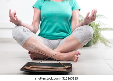 Woman doing yoga in an incense atmosphere