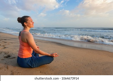 Woman doing yoga - meditate and relax in Padmasana Lotus asana pose with chin mudra outdoors at tropical beach on sunset