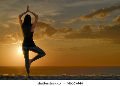 Woman doing yoga and meditation in front of the sea
