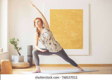 Woman doing yoga in the morning at her home with big gold painting on the wall