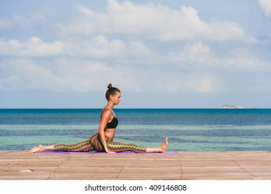 Woman doing yoga in the morning at the sea. Young woman doing the splits outdoor.