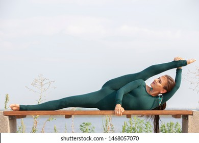 Woman doing yoga near river, enjoying good weather and positive energy in nature. Portrait.