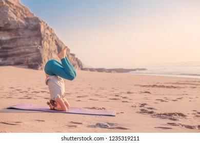A woman doing yoga on a beach, sunset light